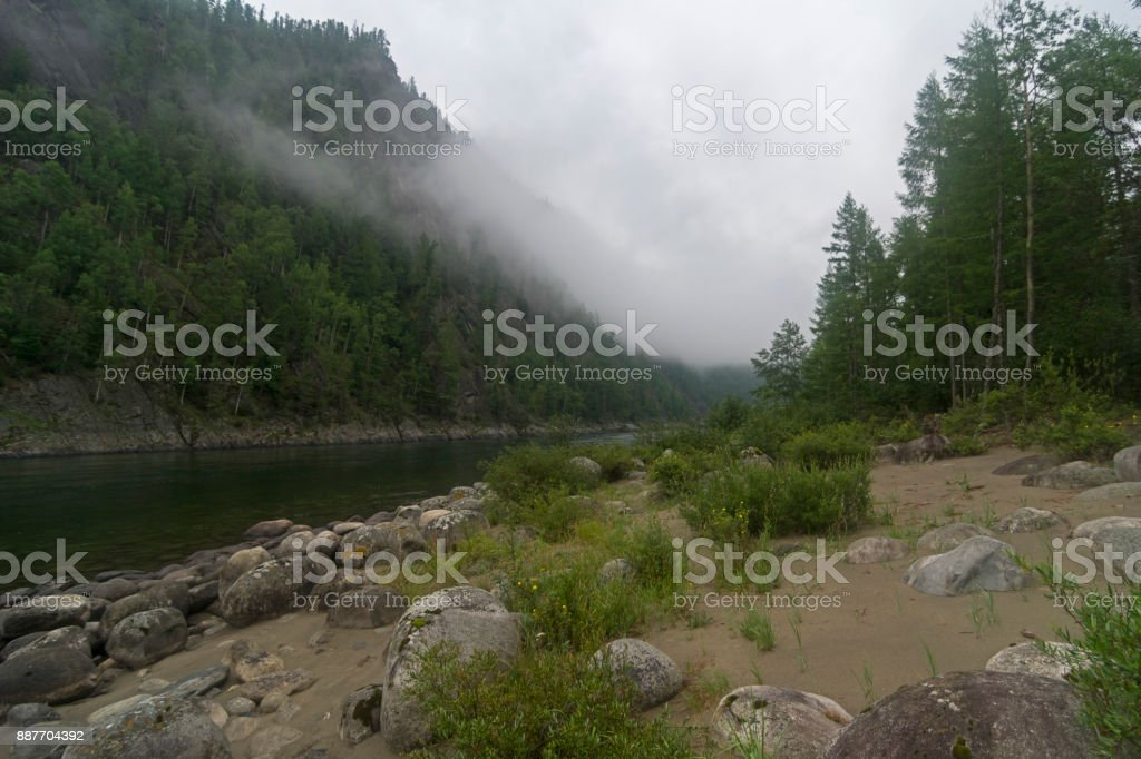 Very low clouds over a mountain river. stock photo