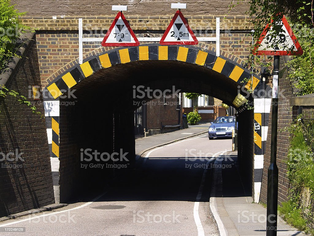 Very low, narrow railway bridge with multiple warning symbols royalty-free stock photo