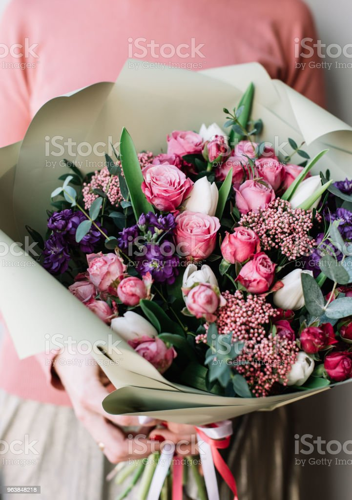 Very nice florist woman holding a beautiful colourful blossoming flowers bouquet of fresh roses, carnations, tulips, eucalyptus on the grey wall background - Royalty-free Adult Stock Photo