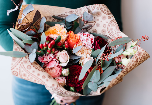 Very nice florist woman holding a big beautiful fresh flower bouquet of roses, pink ranunculus, carnations, eucalyptus in pastel pink and vivid red colors on the grey wall background, close up view