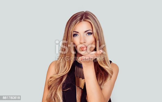 istock Very nice girl with blue eyes blowing giving a virtual kiss isolated light grey white background with copy space 881780818
