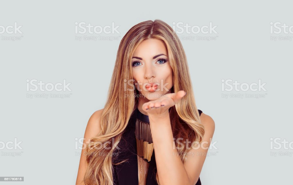 Very nice girl with blue eyes blowing giving a virtual kiss isolated light grey white background with copy space stock photo