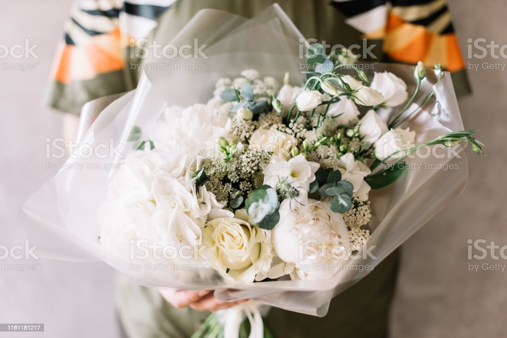 Very Nice Young Man Holding Beautiful Blossoming Flower Bouquet Of Fresh White Hydrangea Eustoma Peony Roses Freesia Eucalyptus On The Grey Wall Background Stock Photo Download Image Now Istock