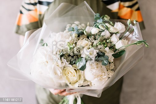 Very nice young man holding beautiful blossoming flower bouquet of fresh white hydrangea, eustoma, peony, roses, freesia, eucalyptus on the grey wall background