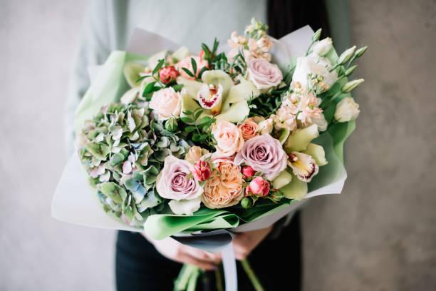 très belle jeune femme tenant un beau bouquet de fleur fleurir frais hortensia, roses, des mattiolas dans les couleurs violets et blancs verts sur le fond du mur gris - bouquet de fleurs photos et images de collection