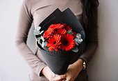 istock Very nice young woman holding a fresh blossoming flower bouquet of vivid crimson red gerbera mini and eucalyptus on the grey wall background 948664846