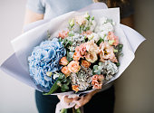 Very nice young woman holding beautiful blossoming bouquet of fresh hydrangea, calla lilies, carnations, roses, mattiola, eustoma, eucalyptus flowers in pink and peach colours on the grey background