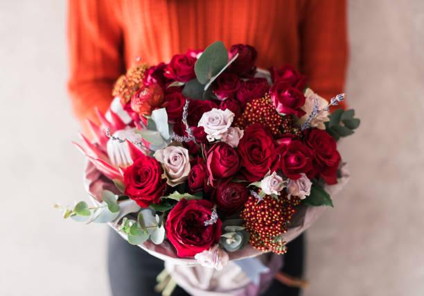 zeer mooie jonge vrouw in rode trui houden bloeiende bloemboeket van verse rozen, anjers, eucalyptus in levendige rode gepassioneerd kleuren op de muur van de grijze achtergrond - boeket stockfoto's en -beelden