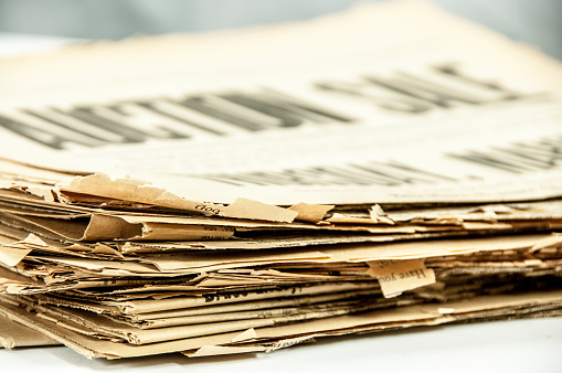 istock Very old, 110 years, newspaper stack on white  copy space 653962290