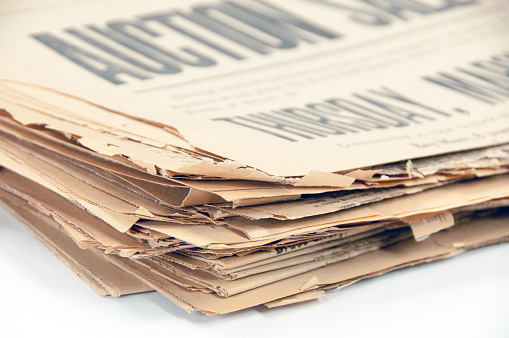 istock Very old, 110 years, newspaper stack on white  copy space 653962406