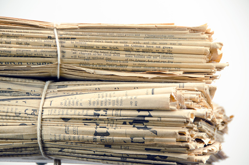 istock Very old, 110 years, newspaper stack on white  copy space 653962550