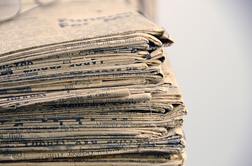 istock Very old, 110 years, newspaper stack on white  copy space 653962660
