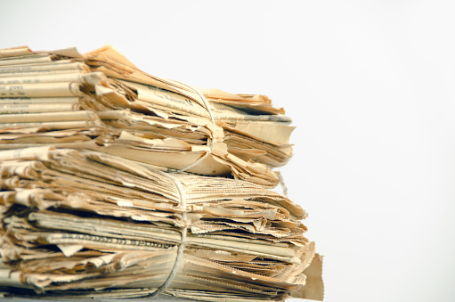 istock Very old, 110 years, newspaper stack on white  copy space 653963102