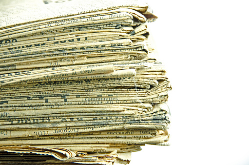 istock Very old, 110 years, newspaper stack on white  copy space 653963210