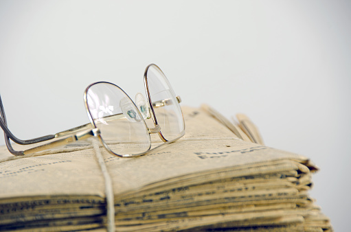 istock Very old, 110 years, newspaper stack on white  with glasses 653962190