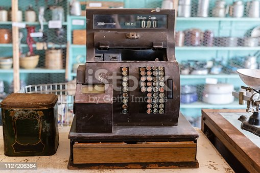 horizontal image of a very old vintage antique wooden cash register with shelves full of dishes in the background.