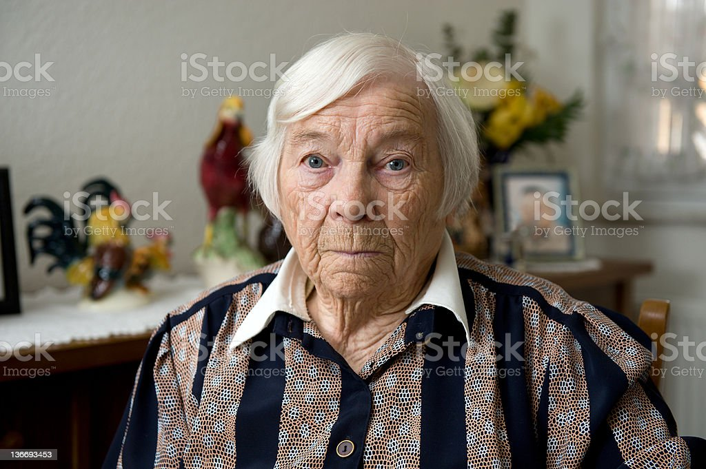 Very old female senior is alone at home stock photo