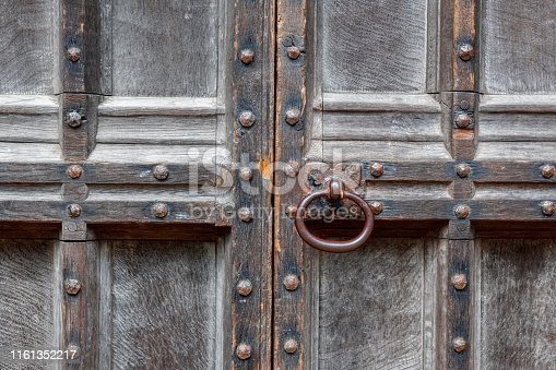 Close up image of a rusty, old-fashioned door knob on an ancient, Gothic-style doorway.