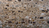 Old gray brown wall made of many different stones - taken in a medieval monastery