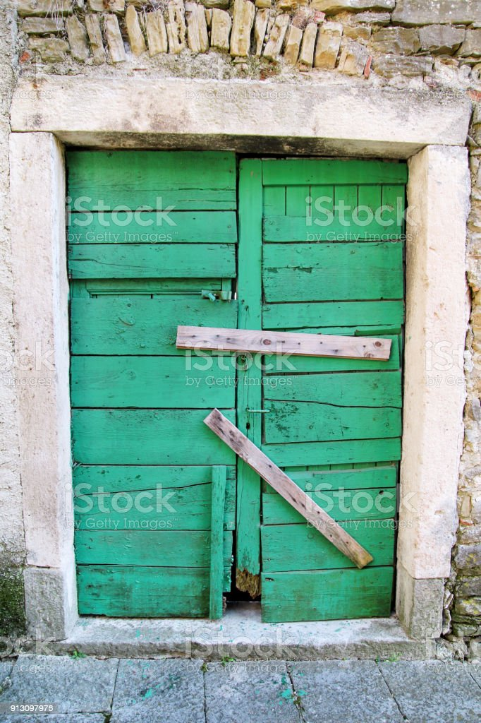 Very old green rustic wood door / Housing insurance. Background, texture and material. stock photo