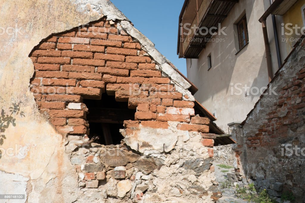 Very old house, falling apart. Cement cladding pealing off house exposing brick. Crumbling wall of an old house in small town of Cesky Krumlov, Czech Republic. stock photo