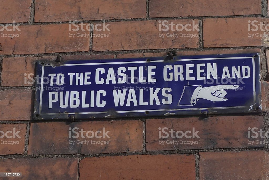 very old porcelain enamel direction sign pointing to castle walks stock photo