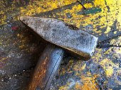 Very old rustic hammer on a wooden work bench.