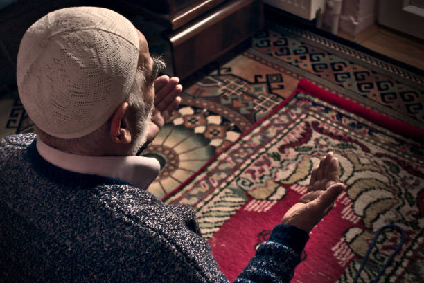 Very old Turkish Muslim man at his 80's praying to Allah at home on his rug stock photo