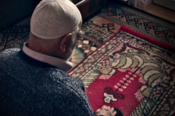 Very old Turkish muslim man doing Salah prayer at his home on his prayer rug stock photo