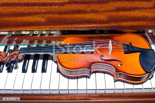 istock Very old violin lying on the piano 828399978