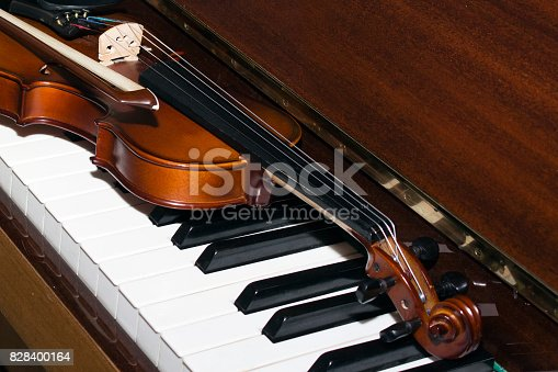 istock Very old violin lying on the piano 828400164