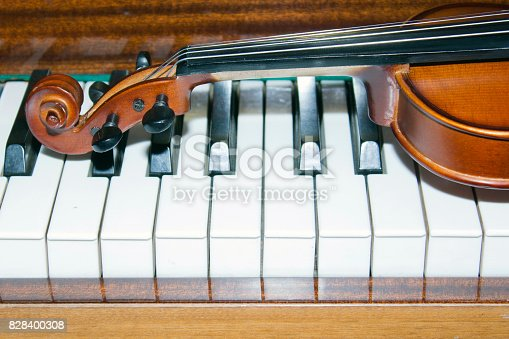 istock Very old violin lying on the piano 828400308