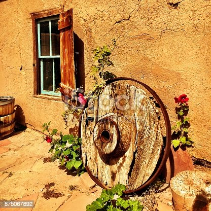 Historic cart wheel in Taos, New Mexico. American Southwest.