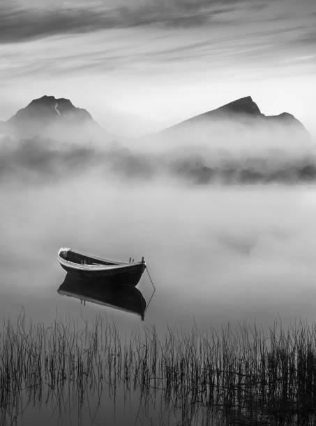 Noite de verão muito pacífica com barco de madeira e nevoeiro em Lofoten, Noruega - foto de acervo