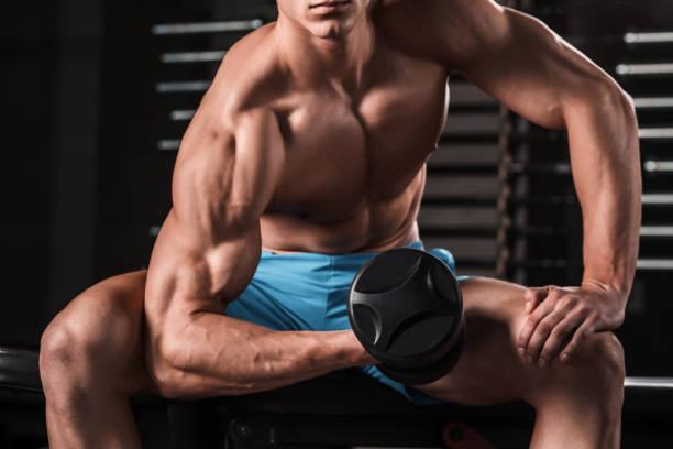macht athletischen kerl bodybuilder führen übung mit hanteln in dunklen turnhalle - killer workouts stock-fotos und bilder
