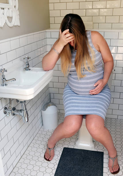 Very pregnant and miserable woman sitting on toilet seat, crying stock photo