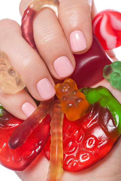 Very pretty pink nails. Beautiful pink nails with candy. pink nail polish stock pictures, royalty-free photos & images