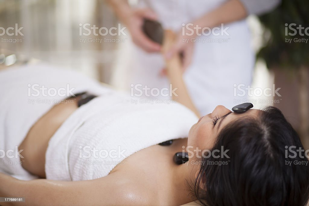 Very relaxed woman getting a hot stone massage royalty-free stock photo