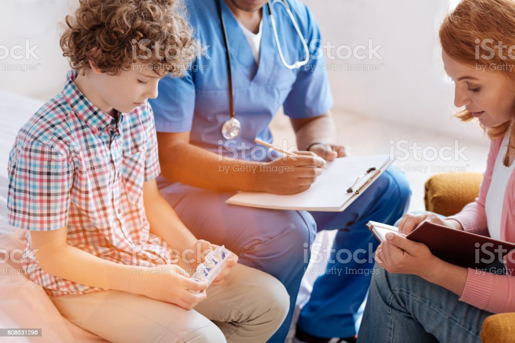Very responsible mother bowing head while making notes stock photo