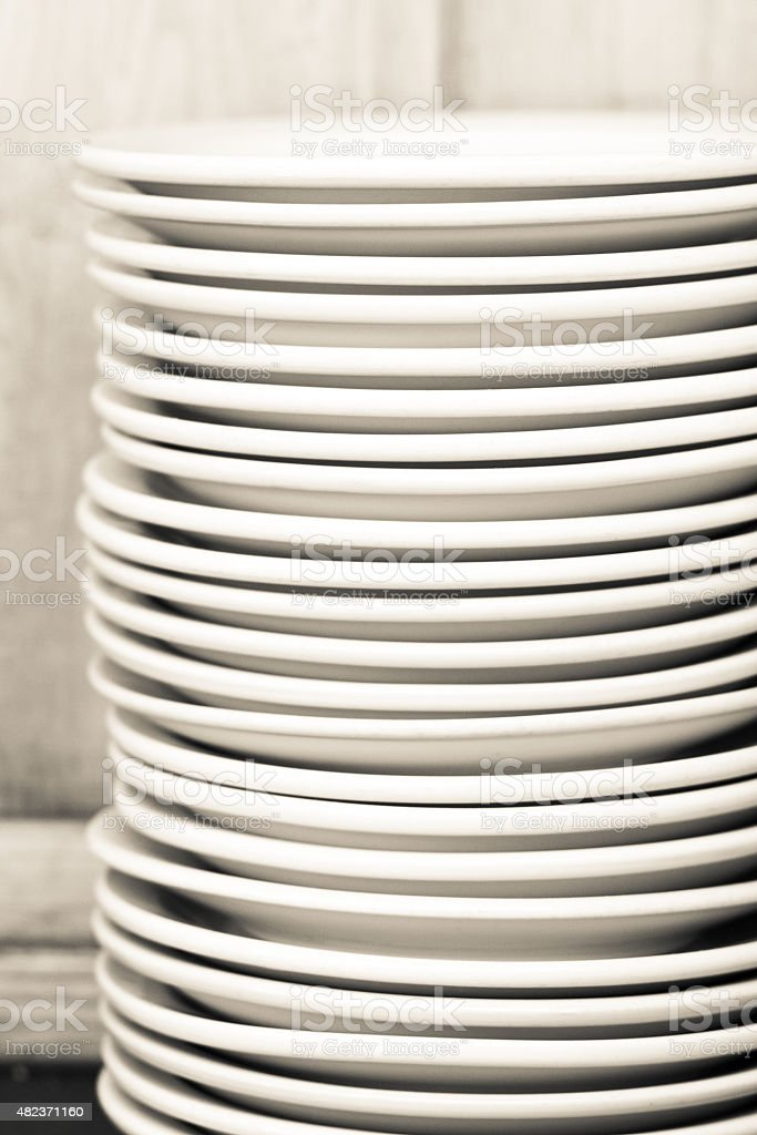 Very Tall Stack of White Restaurant Plates (Close-Up) stock photo