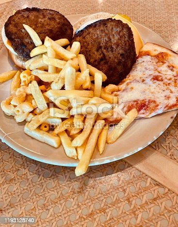 Large helping of french fries with two hamburgers and a slice of pizza makes for a very unhealthy meal.