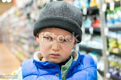 very upset three years old boy looking at the camera wearing a hat at the supermarket