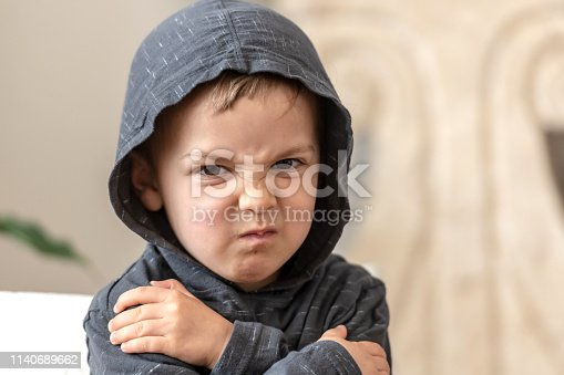 very upset three years old boy looking at the camera wearing a hoodie