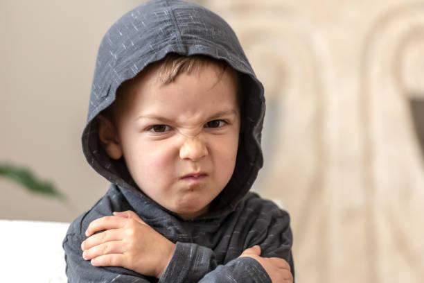 niño muy molesto de tres años mirando la cámara - niño enfado fotografías e imágenes de stock