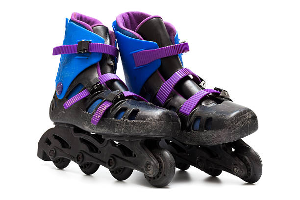 Very worn black roller skates with blue and purple accents stock photo