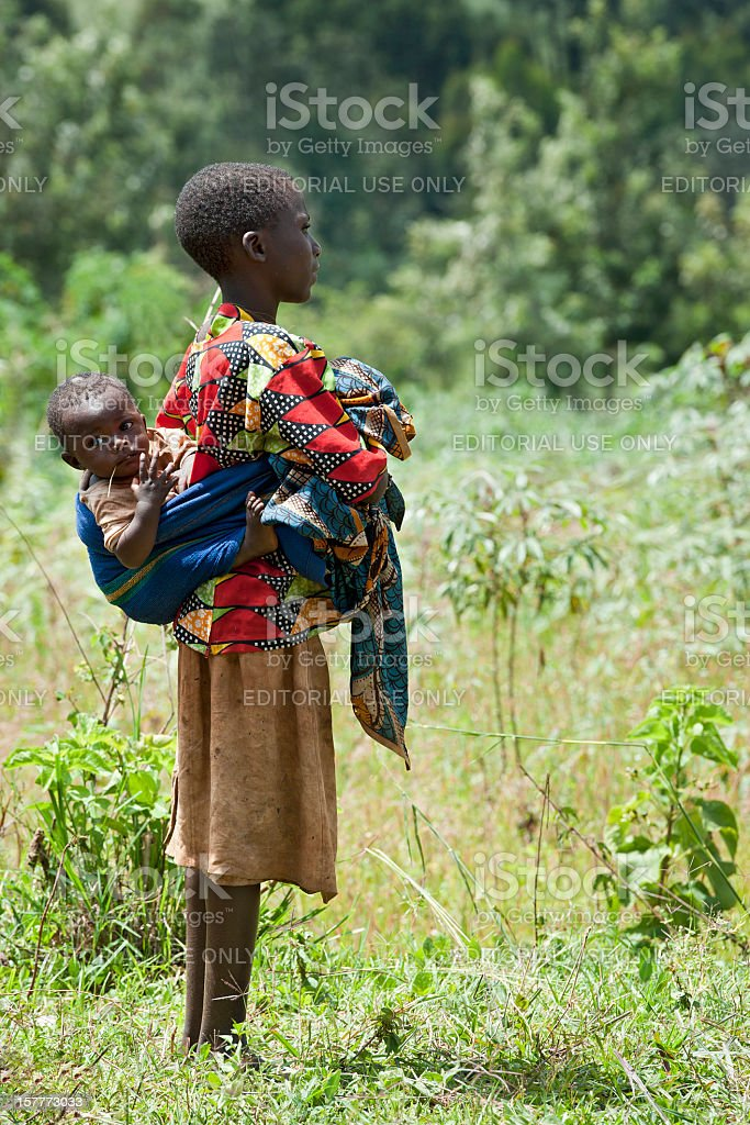 Very young african mother with her baby in a field stock photo