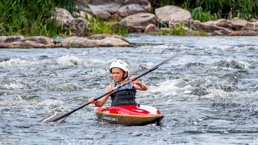 A very young athlete improves his skills in running a kayak. Kayaking is an extreme sport and recreation. stock photo