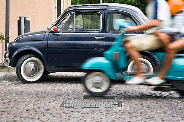 vespa y fiat 500. borroso. imagen de color - vintage vespa fotografías e imágenes de stock