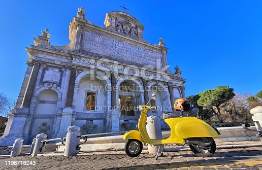 Rome, Italy. December 28, 2019. An Italian style symbol, a yellow Vespa Piaggio, in front of a beutiful monument, the