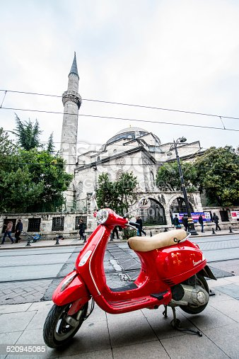 Istanbul, Turkey - October 28, 2014: Vespa Scooter parked in front of Mosque on the street of Istanbul. People walking on the street